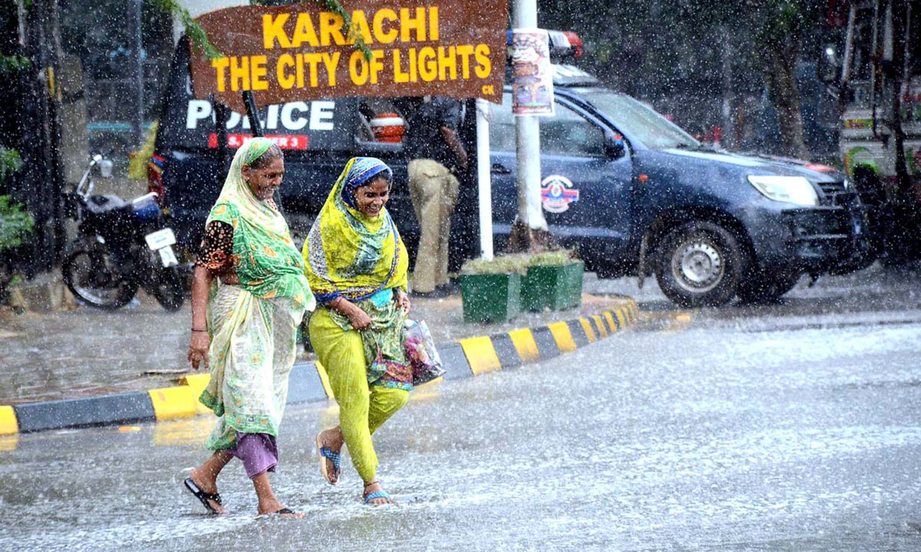 Two women cross a road during rain in Karachi on Thursday. — APP