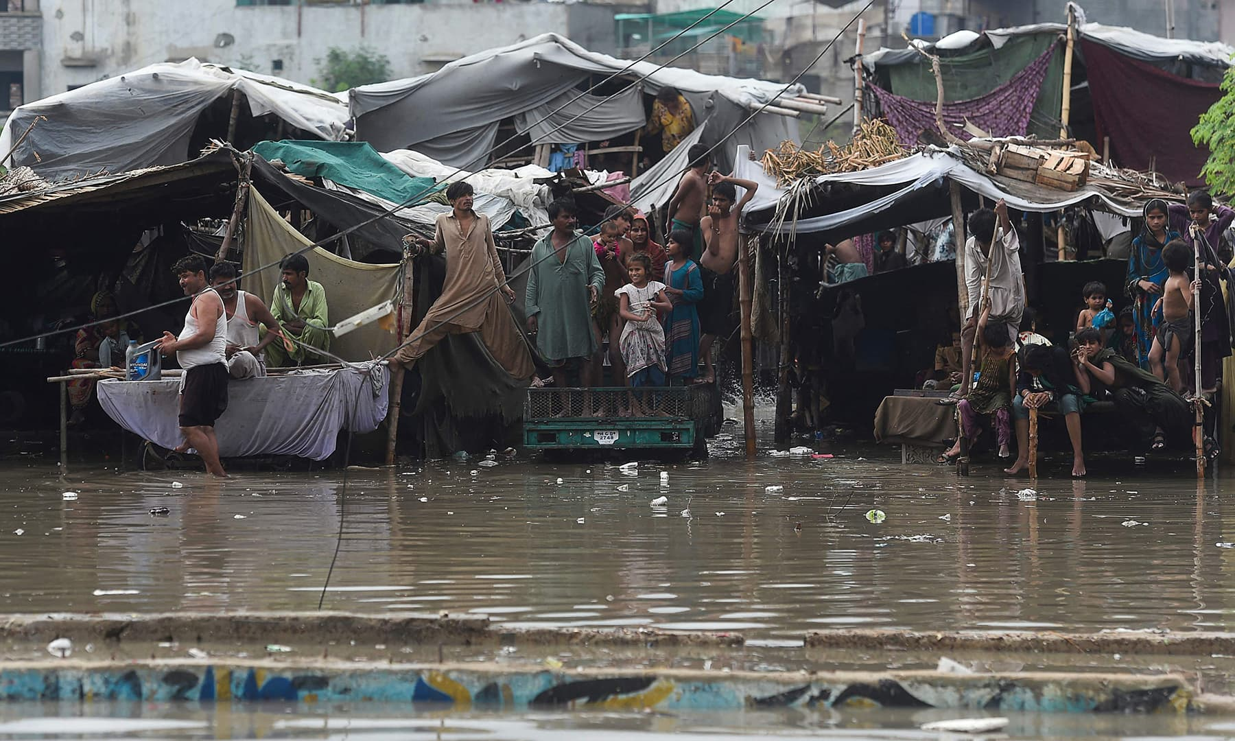 People shelter in their makeshift homes alongside a flooded street after heavy rainfall in Karachi. — AFP