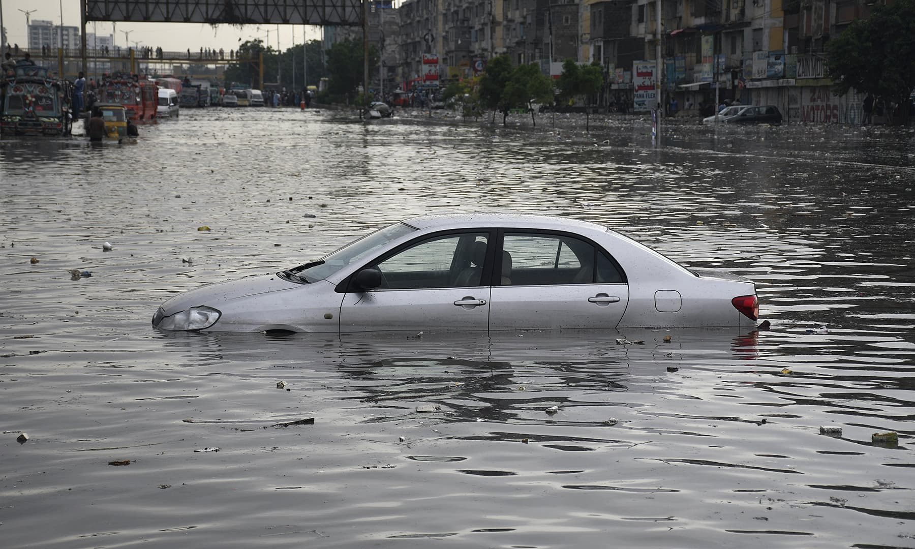 A car is submerged on a road after heavy rainfall in Karachi on Thursday. — AP