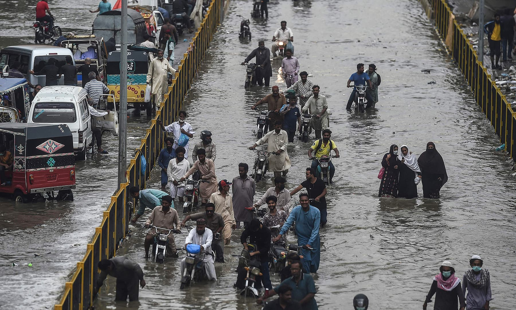 People wade through a flooded street after Thursday's rain in Karachi. — AFP
