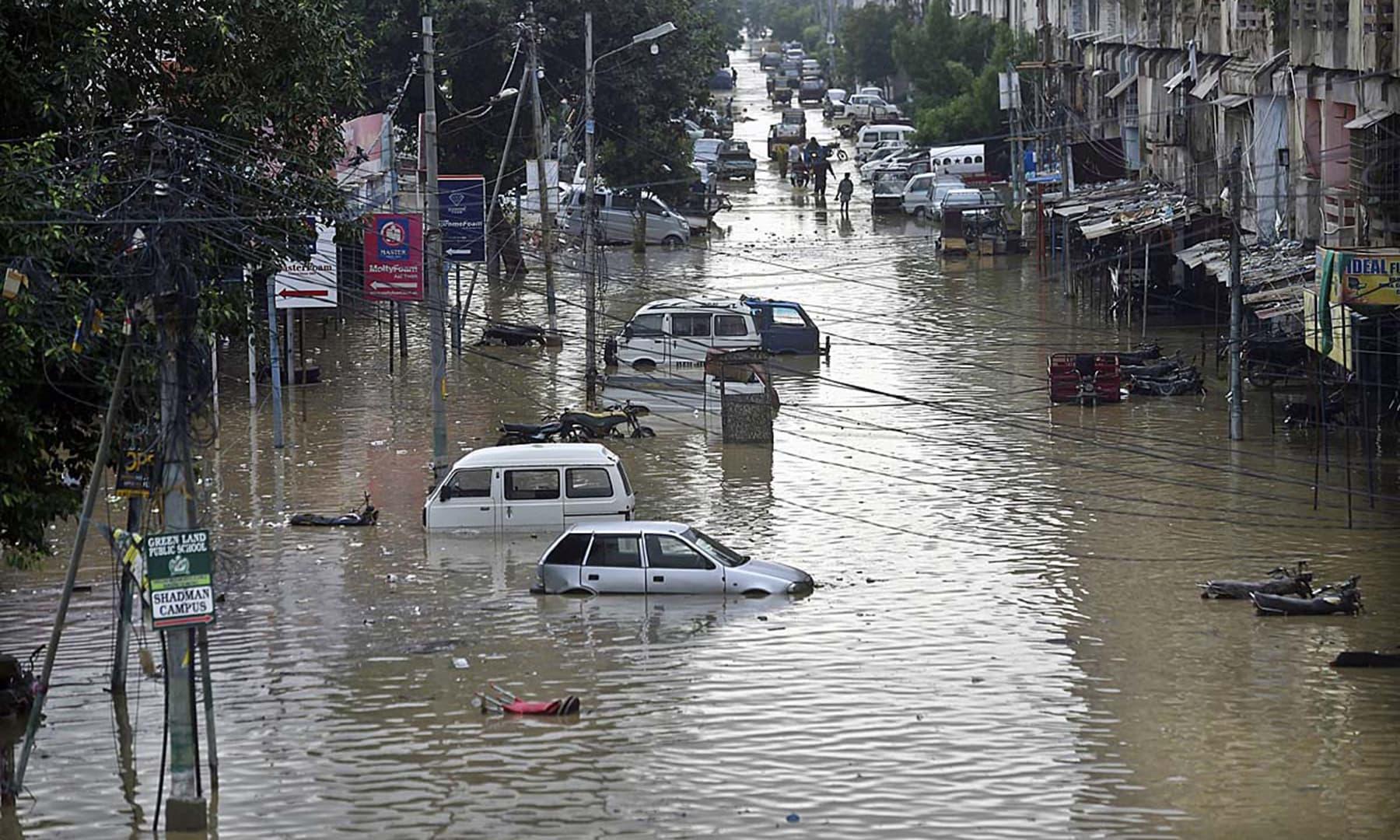 A view of a flooded street at Nagan Chowrangi after heavy monsoon rain in Karachi. — APP