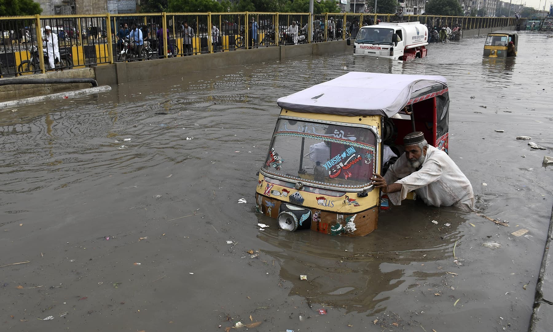 A rickshaw driver navigates through a flooded road after heavy rainfall in Karachi, Thursday. — AP