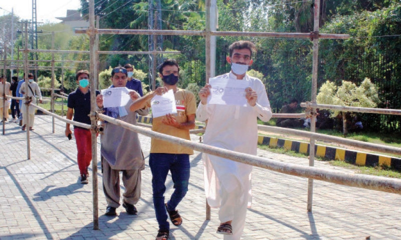 Spectators show their vaccination certificates before entering the cricket stadium to watch National T20 Cup match between the Northern and Balochistan teams on Thursday. — Online