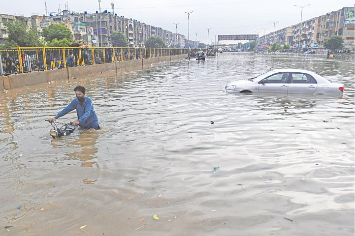 KARACHI: A man pushes his motorbike through a flooded street while a car floats behind after heavy rain on Thursday. As the city received downpour, the authorities warned that the situation was unlikely to improve because the kilometres-long infrastructure of the yet-to-start Green Line bus service had badly affected the Central district's drainage and sewerage system.—AFP