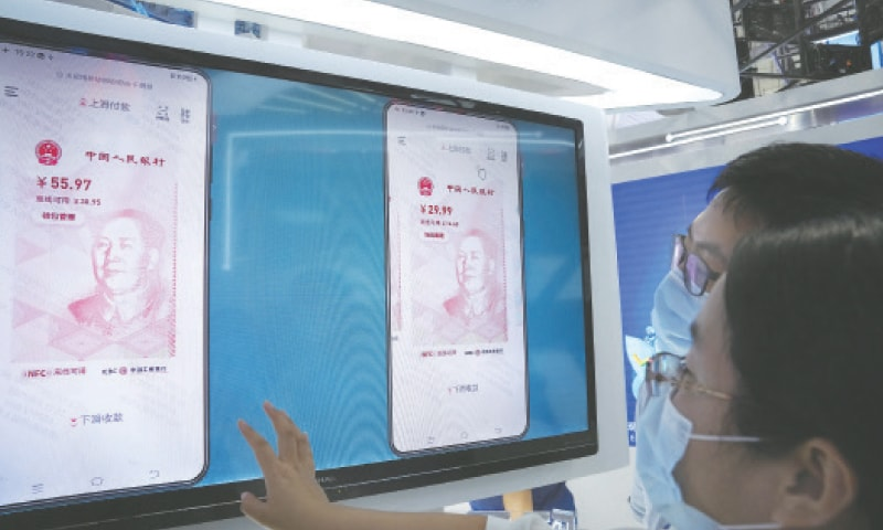 BEIJING: Visitors look at the e-CNY, a digital version of the Chinese Yuan, displayed during a trade fair.—AP