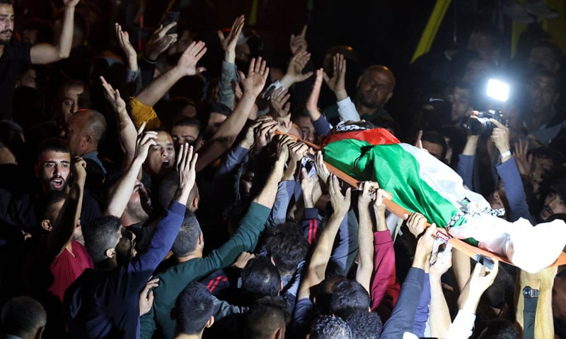 Mourners carry the body of Mohammed Khabisa, a Palestinian who was shot dead by Israeli troops, during his funeral in the West Bank village of Beita. — AFP