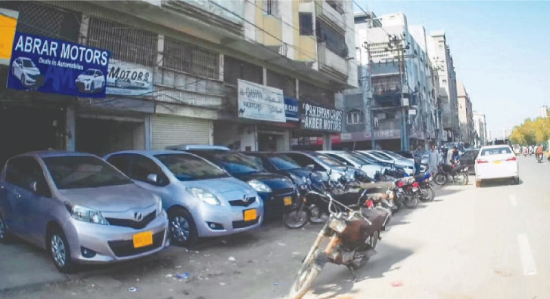 KARACHI: Vehicles are parked outside showrooms on the New M.A. Jinnah Road.—Fahim Siddiqi / White Star
