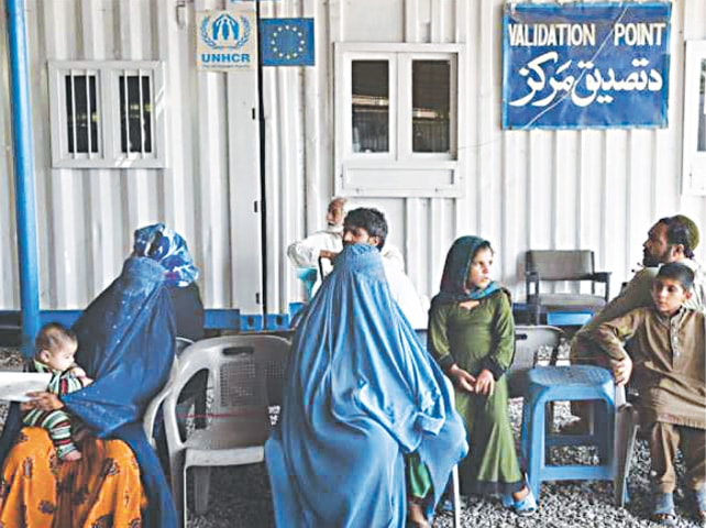 A file photo shows Afghan refugees waiting to get registered at a UNHCR centre in Peshawar   AFP