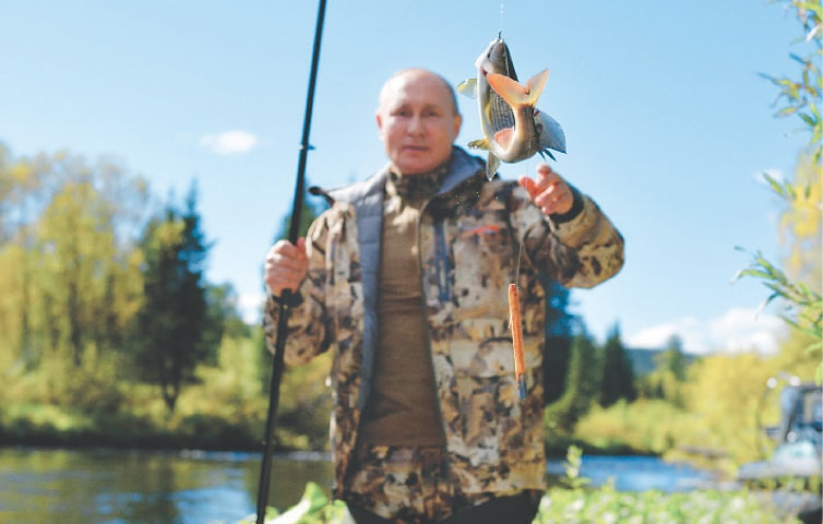 RUSSIAN President Vladimir Putin catches his trophy as he fishes during a visit to the country's far east.—AP