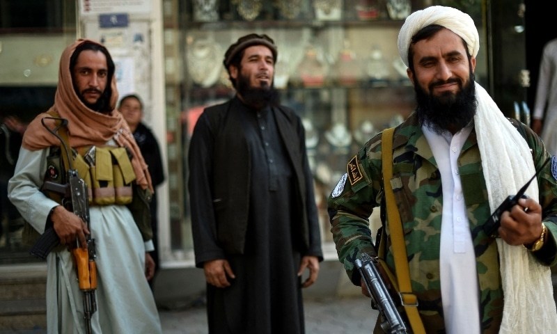 Taliban fighters stand guard on the backdrop of shops selling antiques and decorative merchandise at Chicken Street in Kabul on September 26. — AFP
