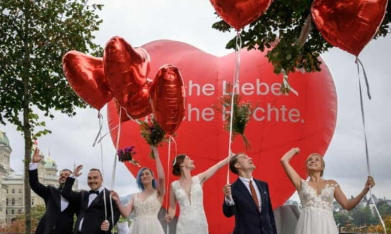 Couples pose during a photo event during a nationwide referendum's day on same-sex marriage in Swiss capital Bern on Sept 26. — AFP