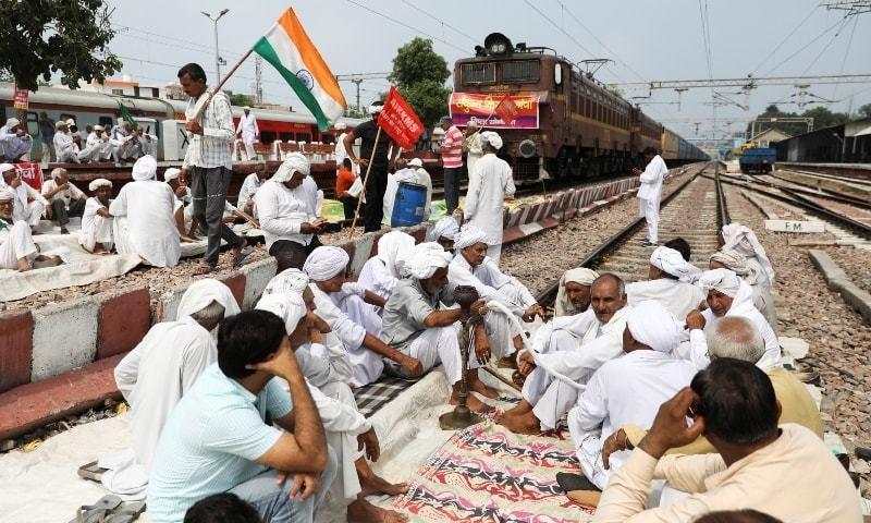 رنگ برنگے جھنڈے لہراتے اور مفت کھانا تقسیم کرتے ہوئے سینکڑوں کسان نئی دہلی کے مضافاتی علاقے میں ایک احتجاجی مقام پر اکٹھے ہوئے۔ - فائل فوٹو:رائٹرز