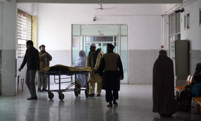 In this file photo,  relatives tend to a man treated at a hospital in Peshawar on December 26, 2015. — AFP