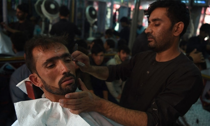 An Afghan barber tends to a customer in Kabul on August 21, 2018. — AFP