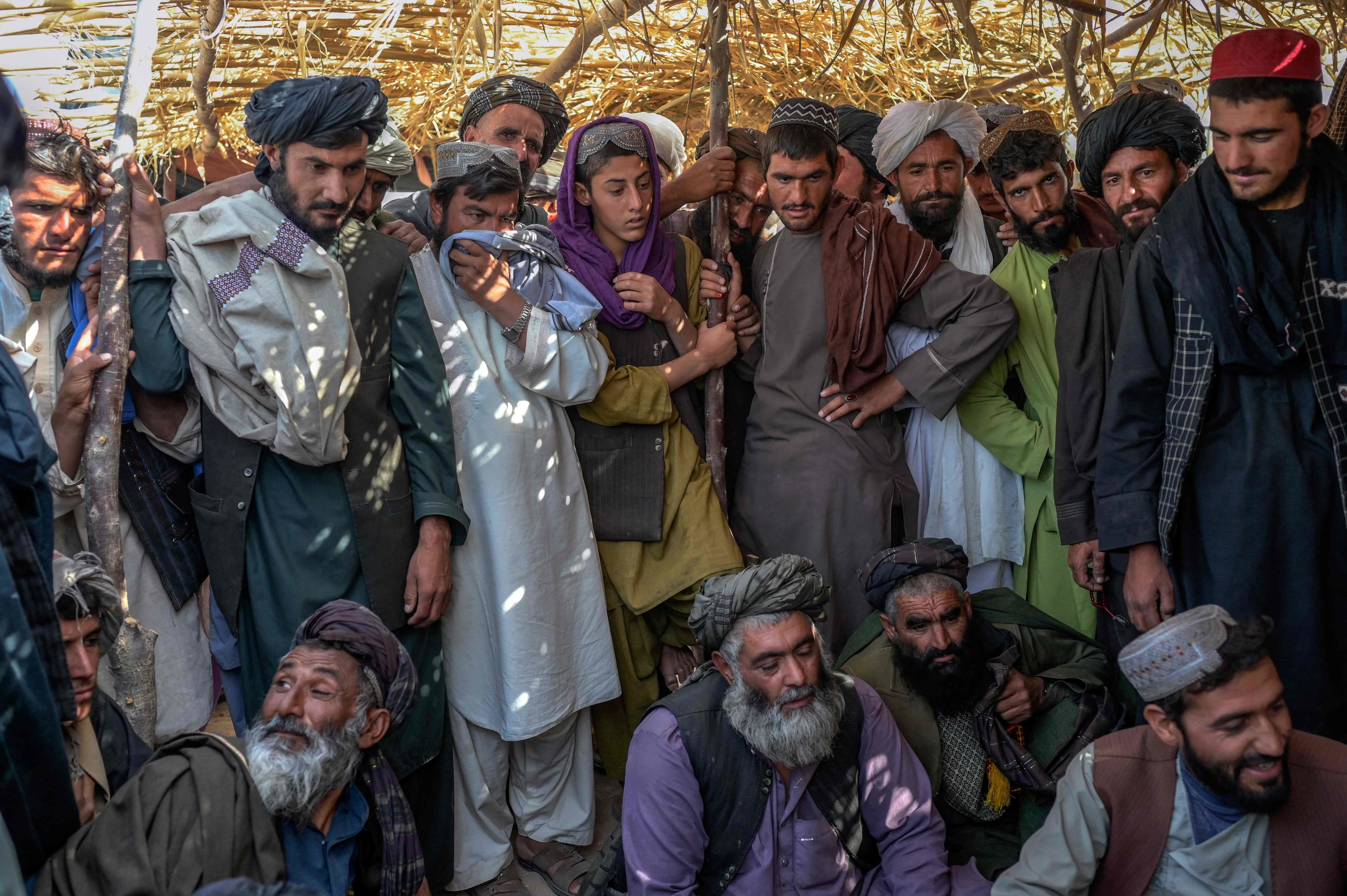 Men gather around bags containing heroin and hashish as they negotiate and check quality at a drug market on the outskirts of Kandahar, Afghanistan on September 24, 2021. — AFP