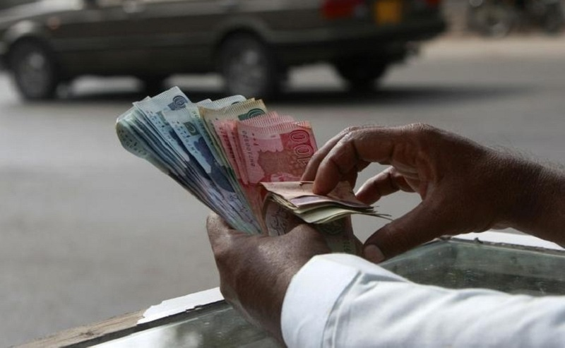 In this file photo, a money changer counts Pakistani rupee notes in Karachi on Sep 23, 2009. — Reuters/File