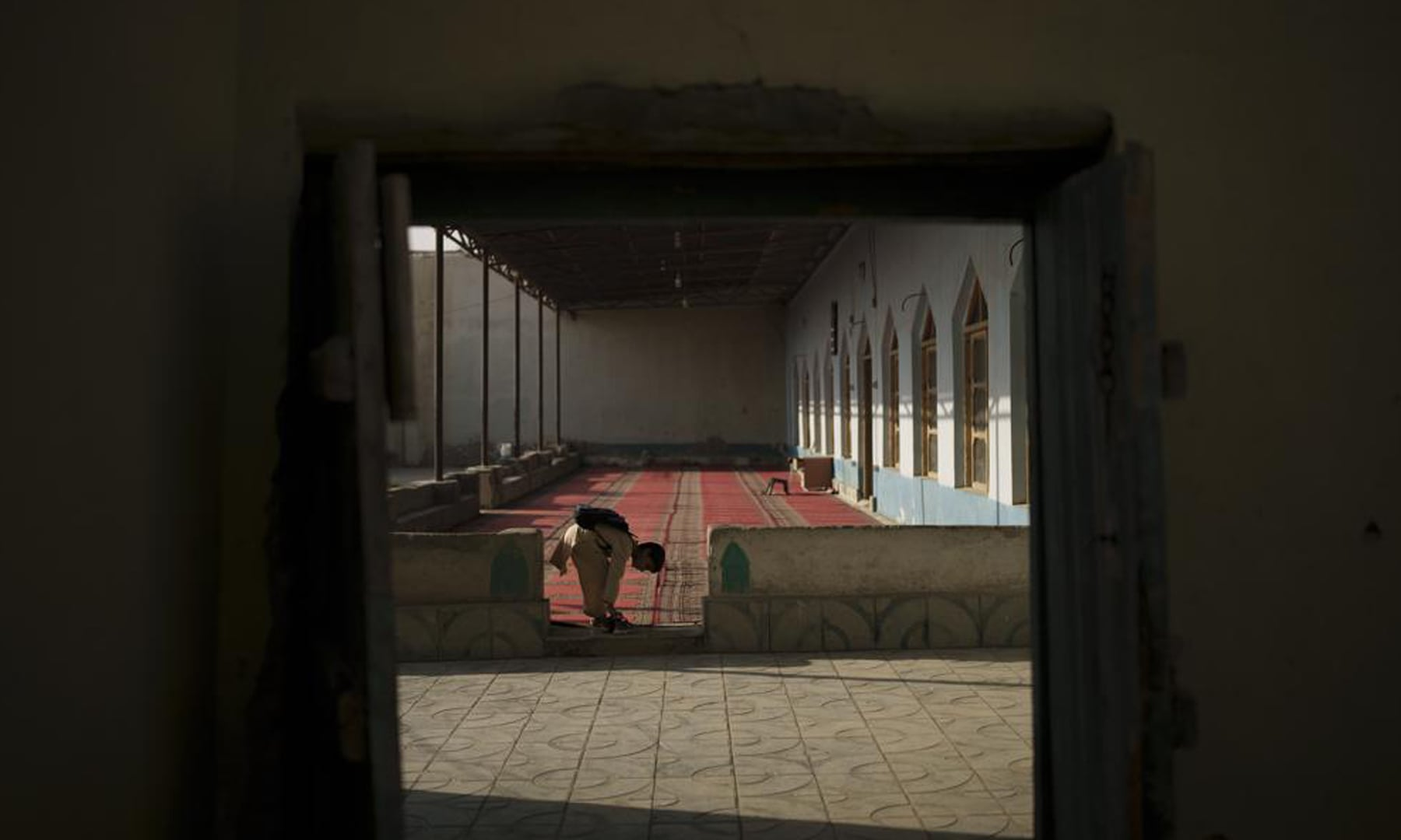 An Afghan boy remove his shoes before entering the mosque for class at a madressah in Kabul, Afghanistan. — AP