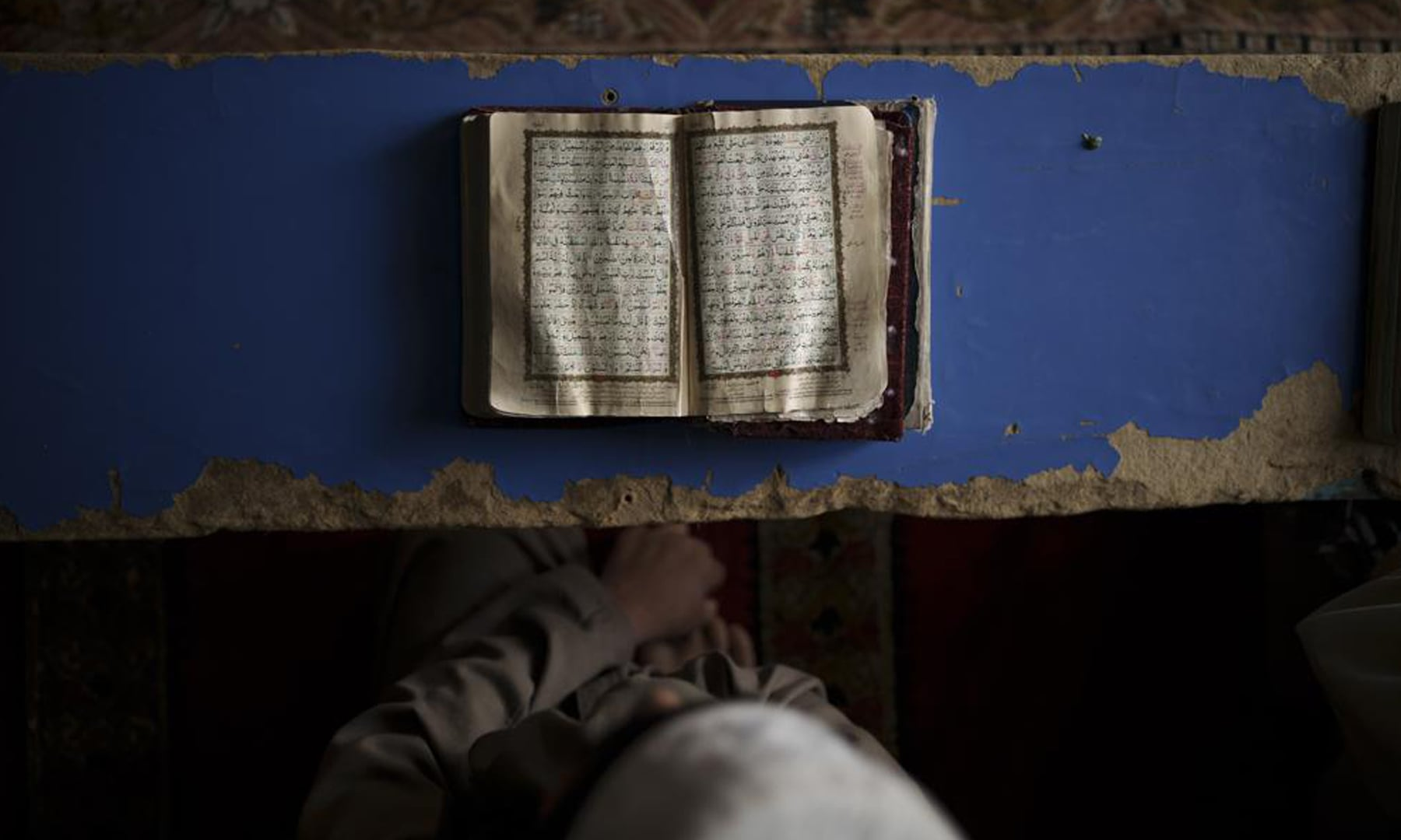 An Afghan student reads the Holy Quran at a madressah in Kabul, Afghanistan. — AP