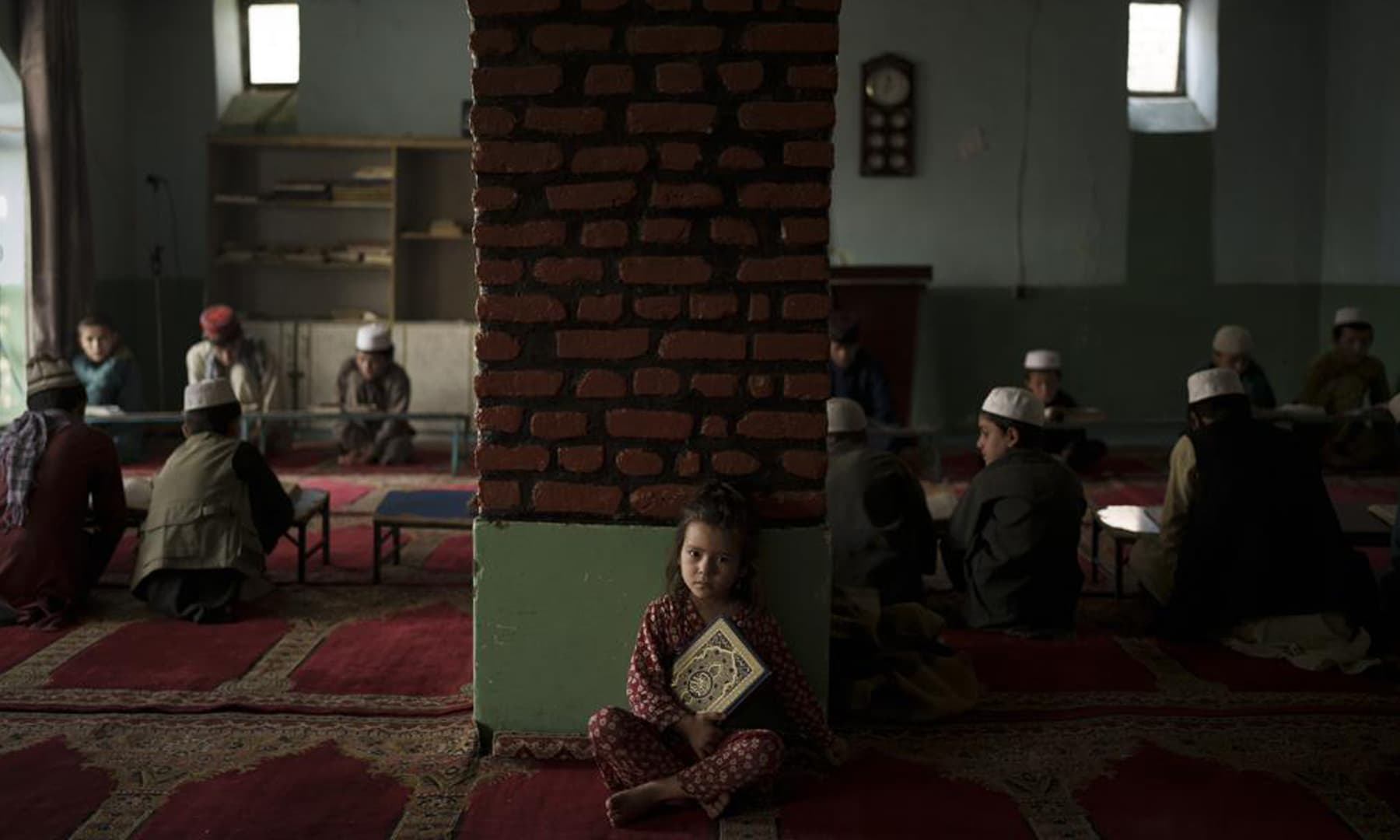 The niece of a teacher sits alone in a classroom as boys attend a class to memorise the Holy Quran at a madressah in Kabul, Afghanistan. — AP