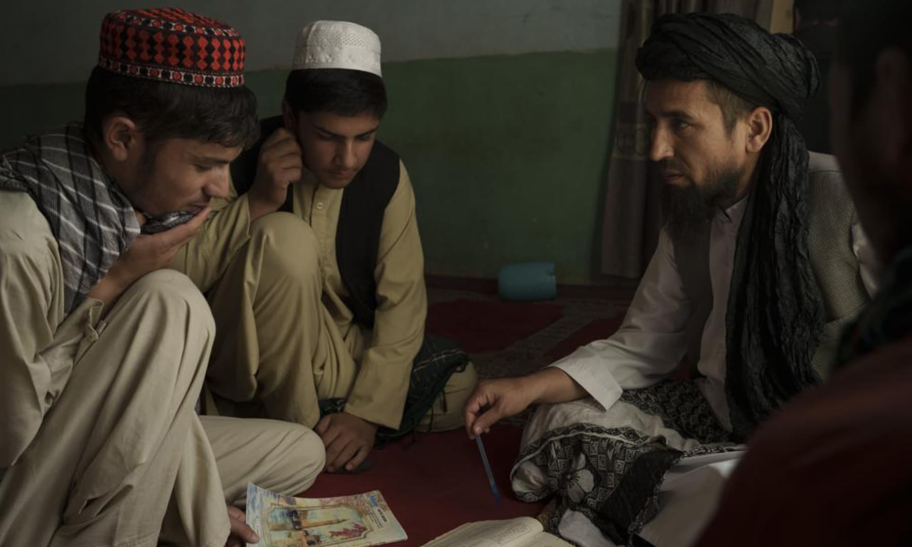 Afghan madrassa director Sebghatullah Samadi (right) talks to students during class at a madressah in Kabul, Afghanistan. — AP