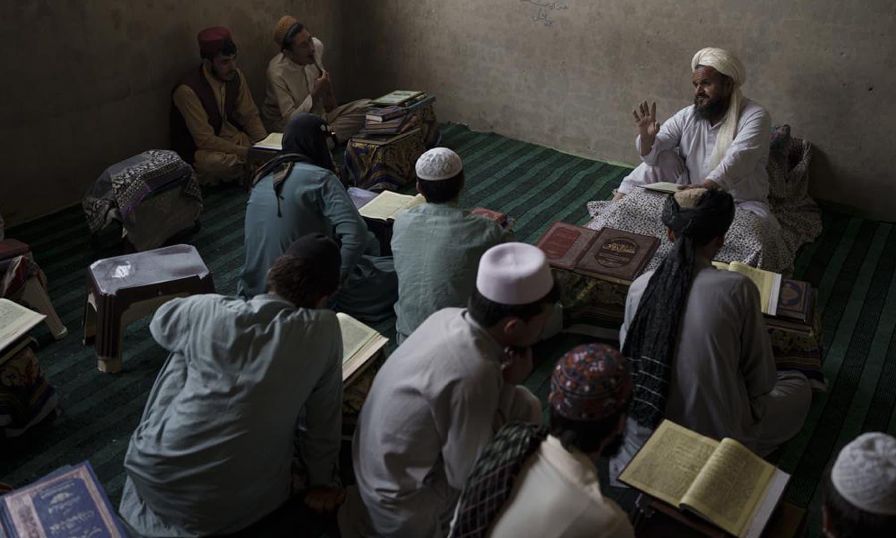 A teacher talks to students during class at the Khatamul Anbiya madressah in Kabul, Afghanistan. — AP