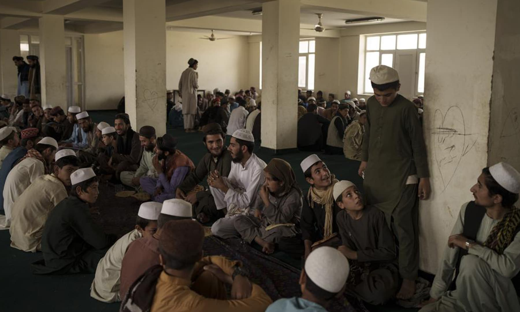 Afghan students wait for breakfast to be served at the dining hall of the Khatamul Anbiya madressah in Kabul, Afghanistan. — AP