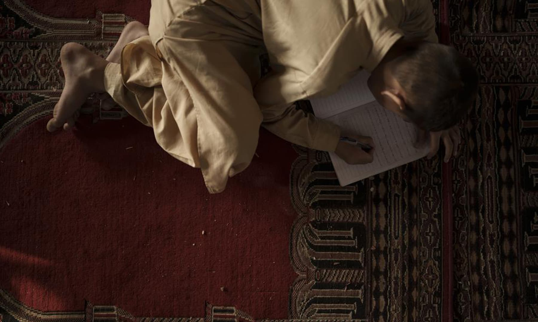 An Afghan student takes notes during class at a madressah in Kabul, Afghanistan. — AP