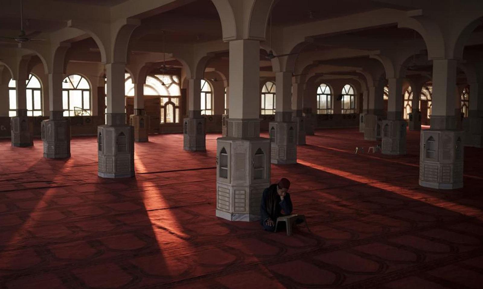 ایک طالبعلم خاتم الانبیا مدرسے کی  مسجد میں قرآن کی تلاوت کررہا ہے—فوٹو: اے پی