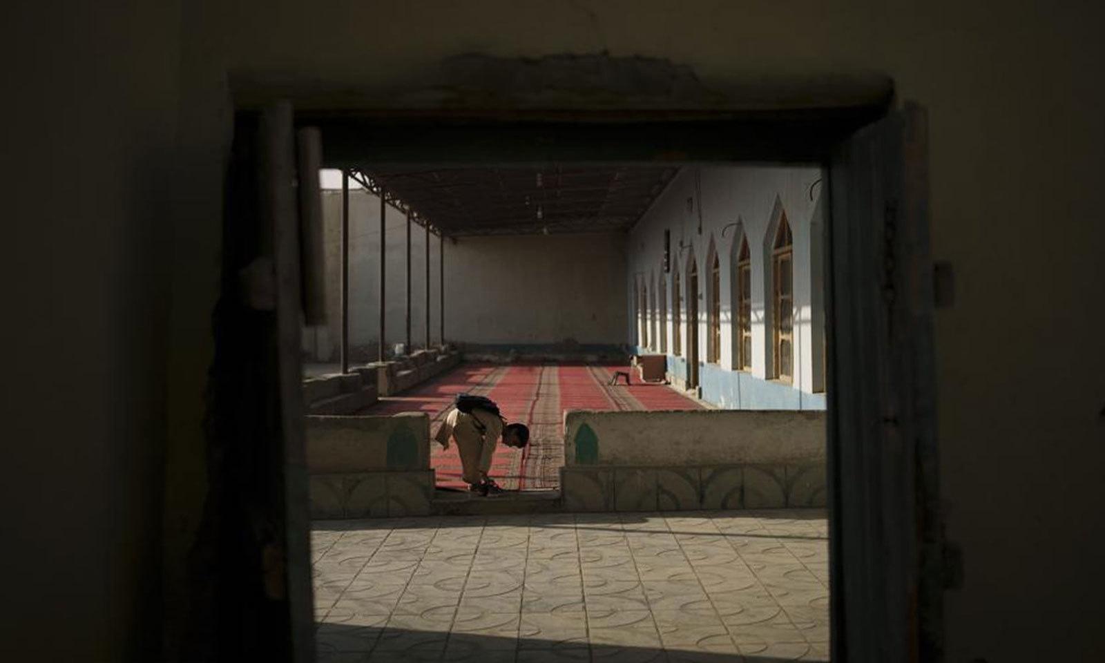 مدرسے کی جماعت میں داخل ہونے سے قبل ایک بچہ اپنے جوتے اتار رہا ہے—فوٹو: اے پی