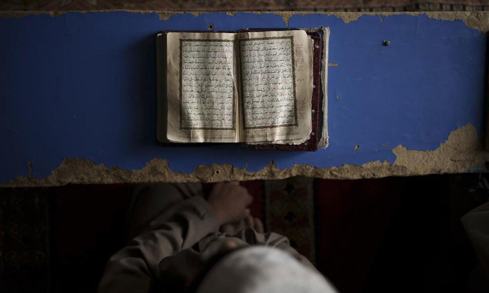 کابل کے ایک مدرسے میں طالب علم قرآن پاک حفظ کررہا ہے — فوٹو: اے پی