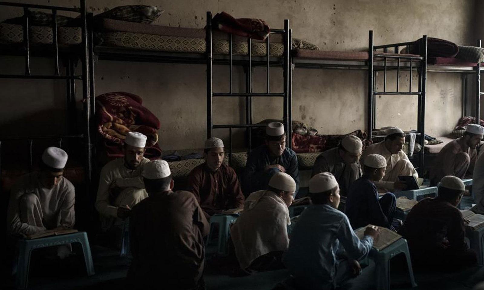 درجنوں نوجوان لڑکے ایک دائرے کی شکل میں بیٹے اپنے استاد عصمت اللہ سبق پڑھ رہے ہیں — فوٹو: اے پی