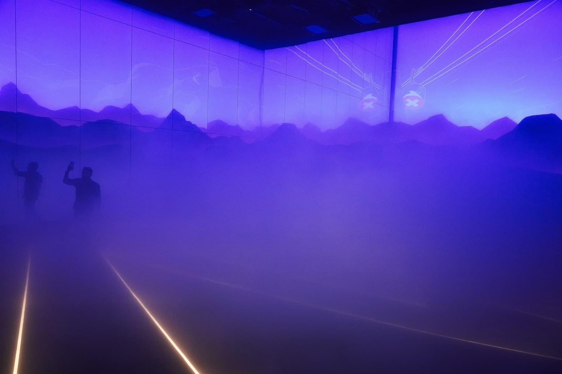A man walks through a foggy mist simulating climbing a mountain inside Switzerland's pavilion. — AP