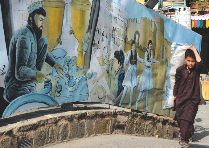 A young boy carrying goods passes by a mural in Islamabad | Mohammad Asim/White Star