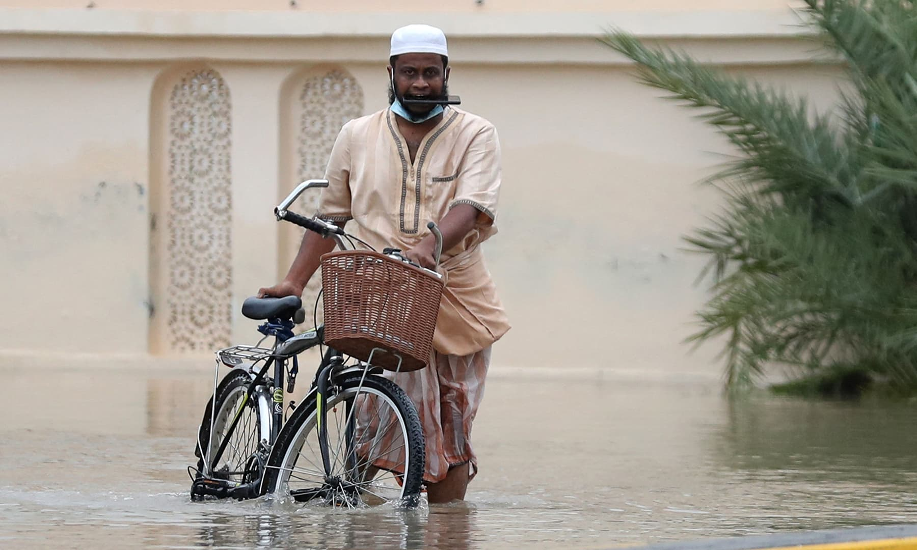 A man wades through a flooded street amid Cyclone Shaheen in Oman's capital Muscat on October 3, 2021. — AFP