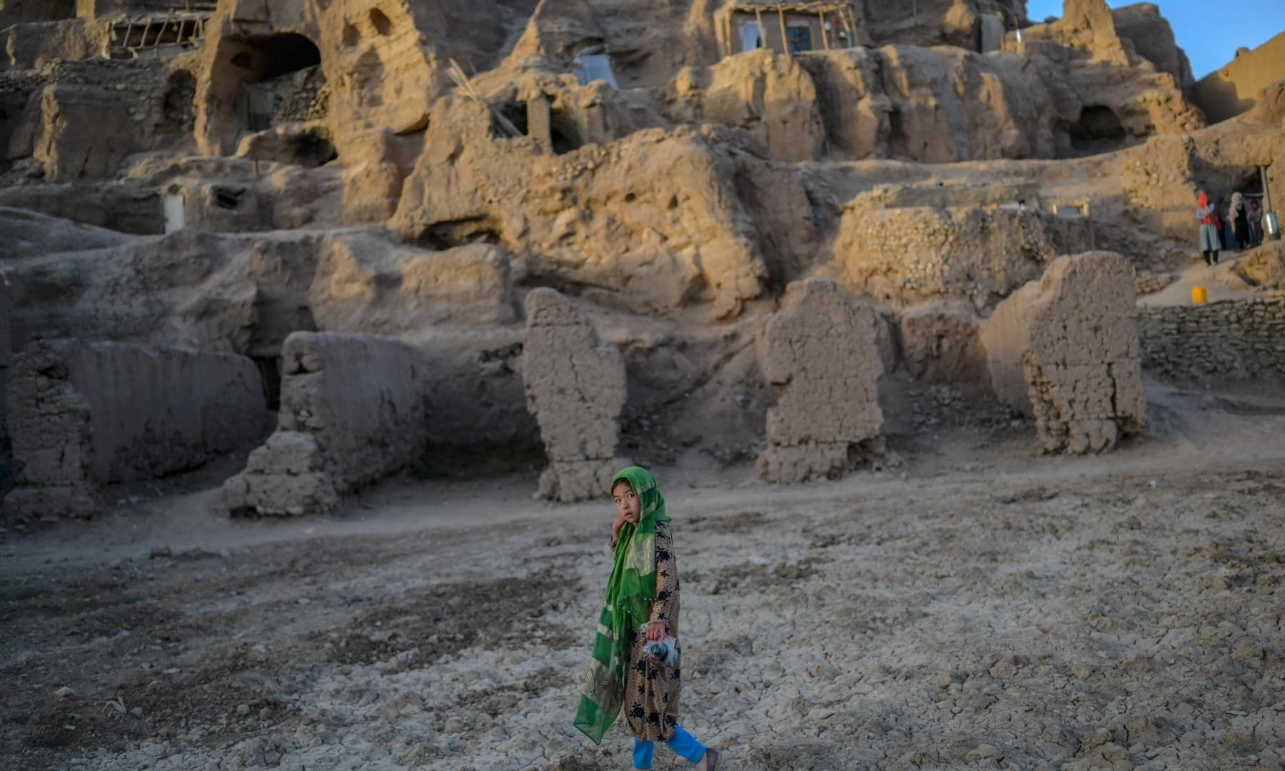 A Hazara ethnic girl walks past the cliffs pockmarked by caves where people still live as they did centuries ago in Bamiyan, Afghanistan on October 3, 2021. — AFP
