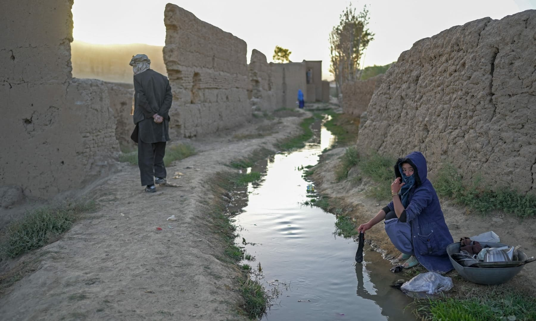 A woman watches while washing clothes and dishes at a village in Bamiyan, Afghanistan on October 3, 2021. — AFP