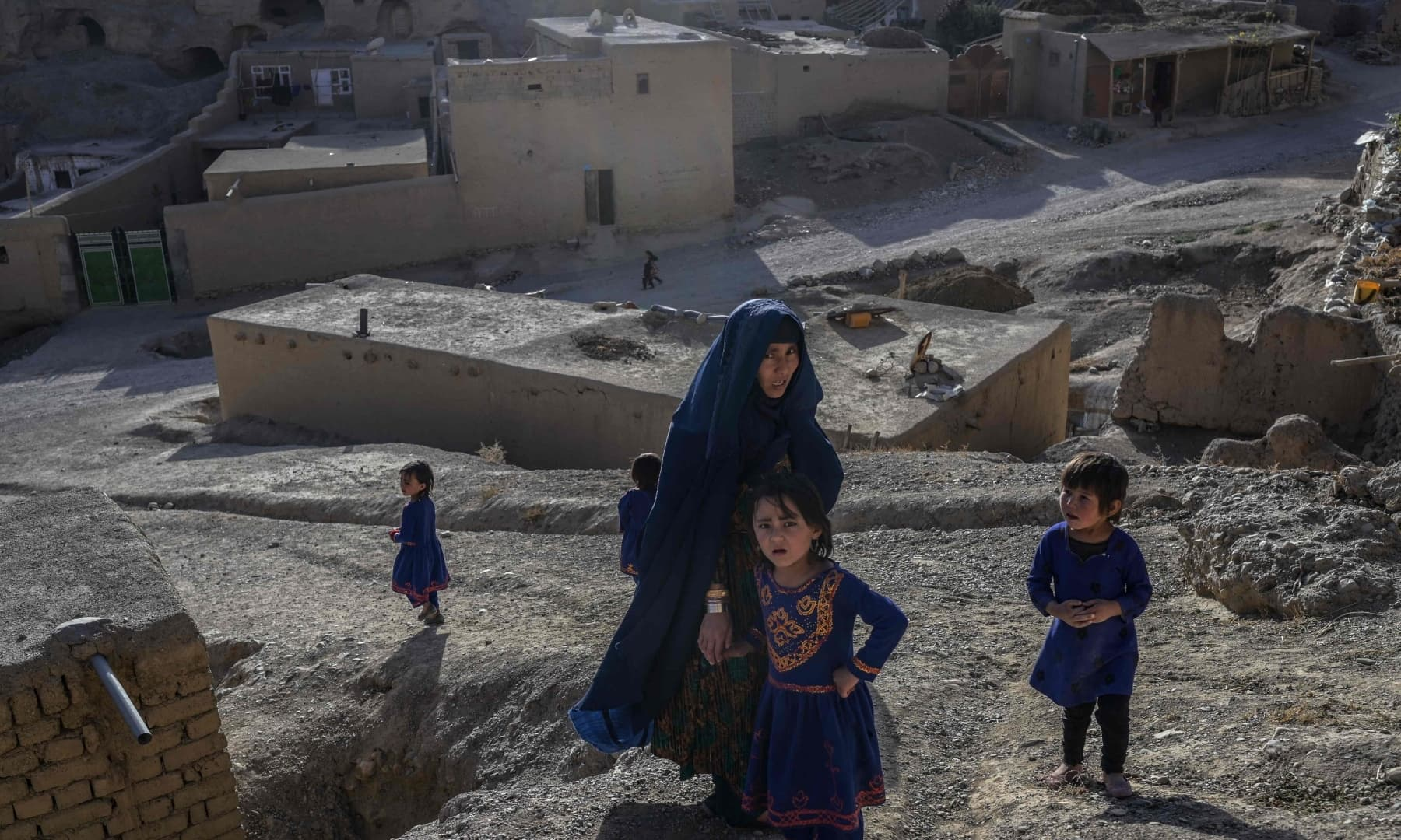 A Hazara ethnic woman and children walk through a village where people still live as they did centuries ago in Bamiyan, Afghanistan on October 3, 2021. — AFP