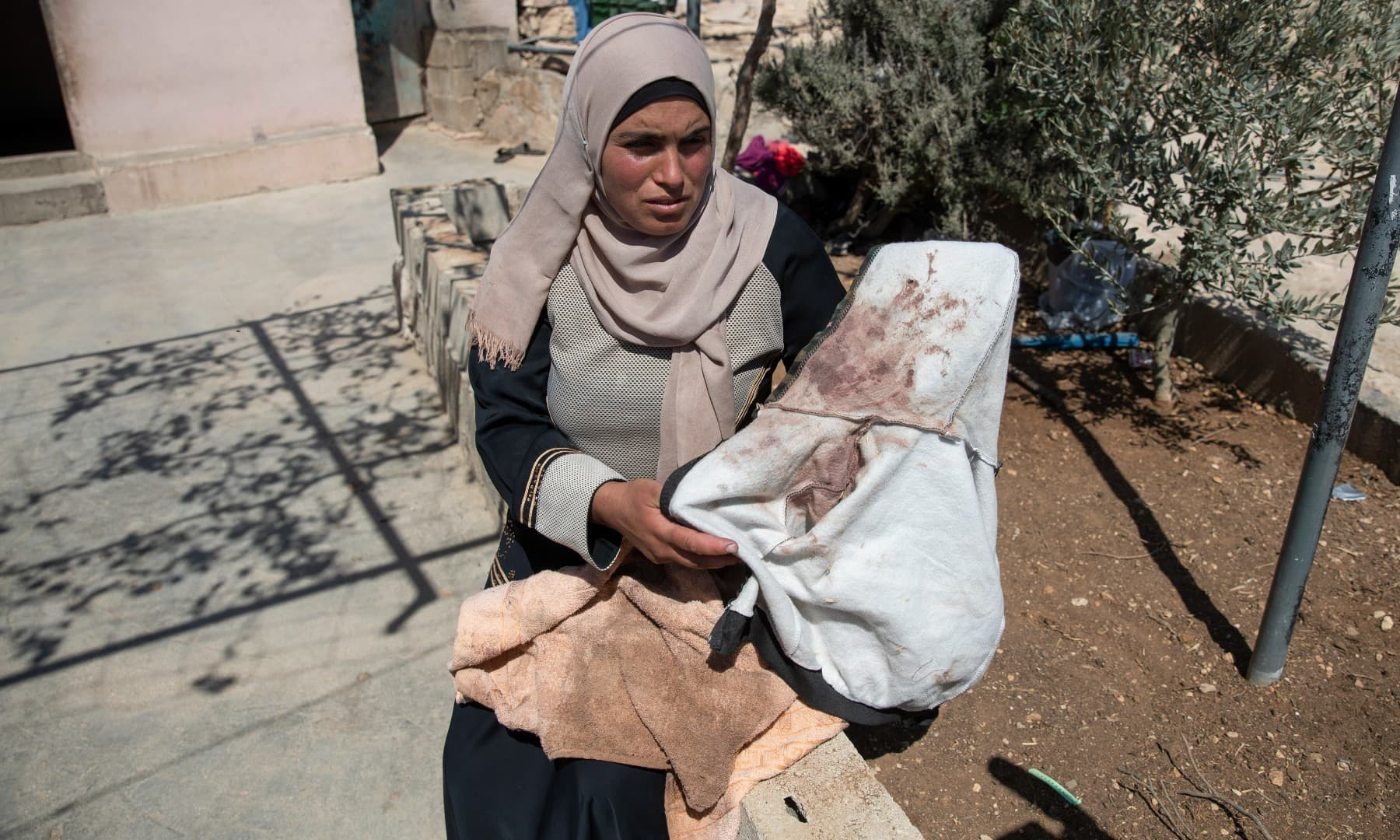 Palestinian mother Baraa Hamamdi holds her injured son's bloodstained clothes that was left behind after Mohammed was evacuated to an Israeli hospital, following a settlers attack on her Palestinian Bedouin community, in the West Bank village of Al-Mufagara, on Sept 30. — AP