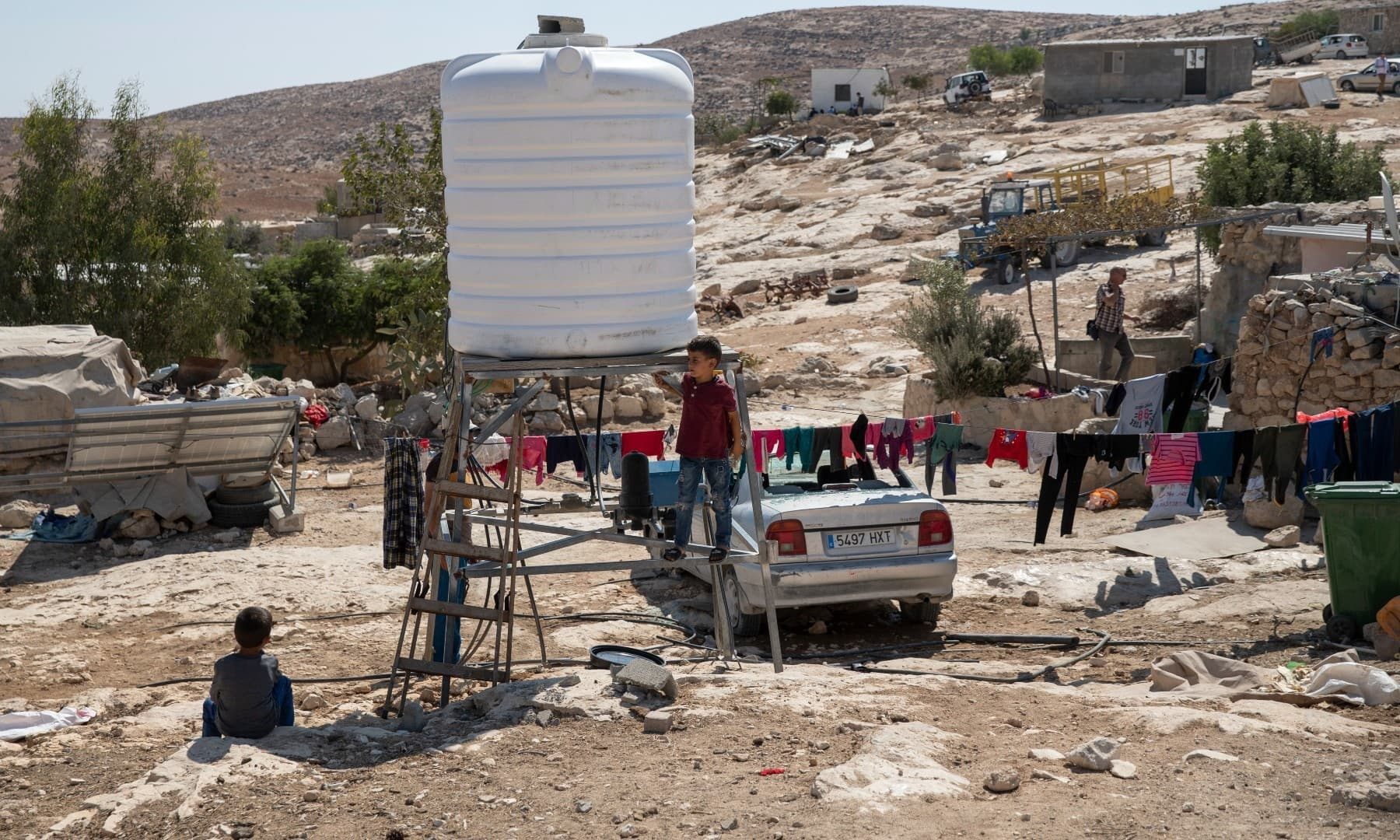Children play by a new water tank that replaced a damaged one following a settlers' attack from nearby settlement outposts on the Palestinian Bedouin community, in the West Bank village of Al-Mufagara, on Sept. 30. — AP