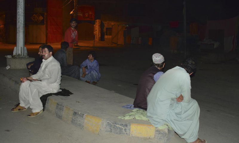 People gather outside their houses following a severe earthquake, in Quetta on Thursday. — AP