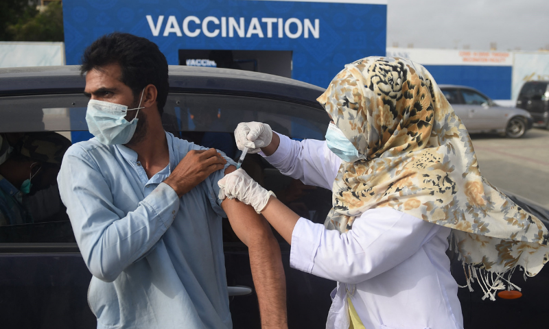 A man receives a dose of the Sinopharm vaccine, during a drive-through vaccination in Karachi. — AFP/File