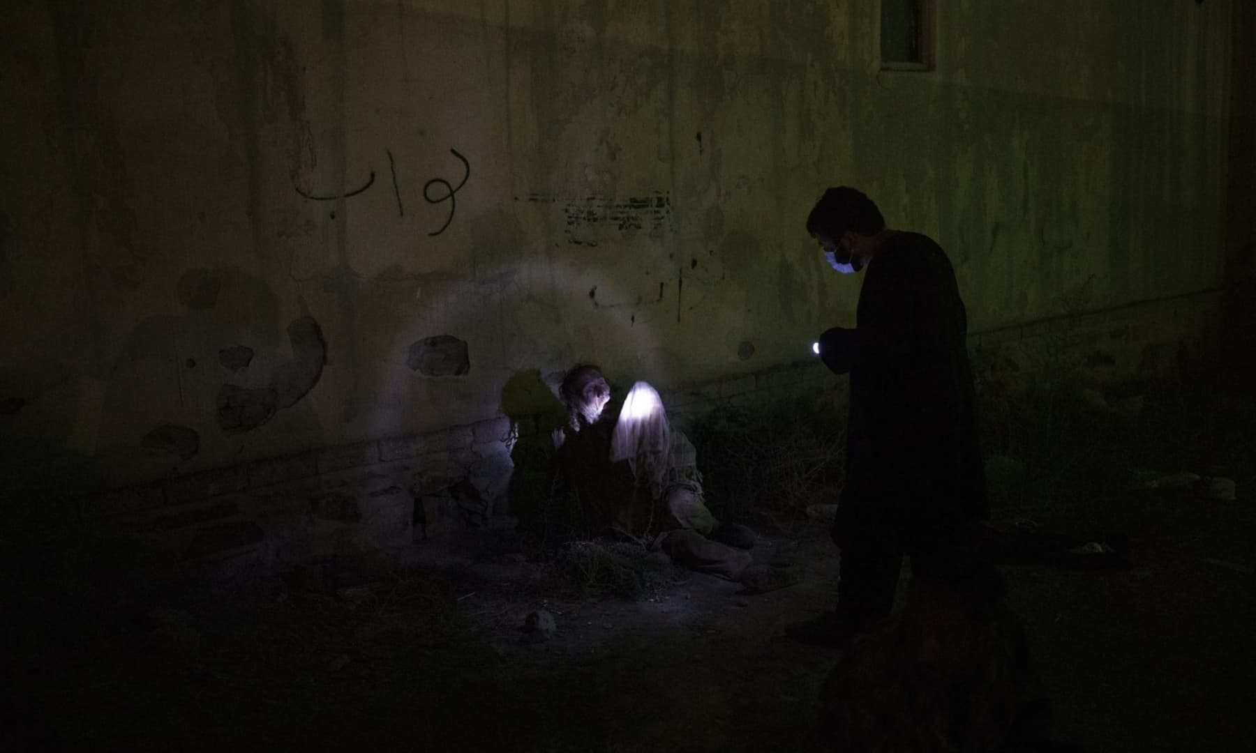 A Taliban fighter uses a flashlight to wake up a drug user detained during a police raid in Kabul, Afghanistan, October 1, 2021. — AP