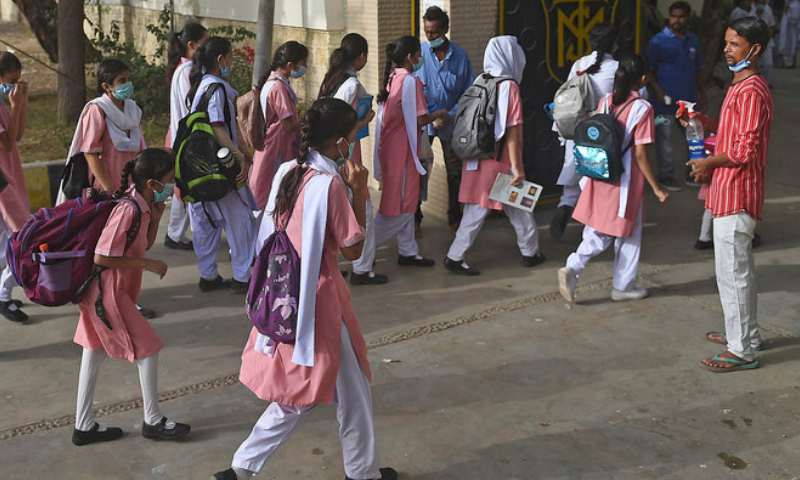 A staff member helps school children sanitise their hands before entering the premises of a school in Karachi. — AFP/File