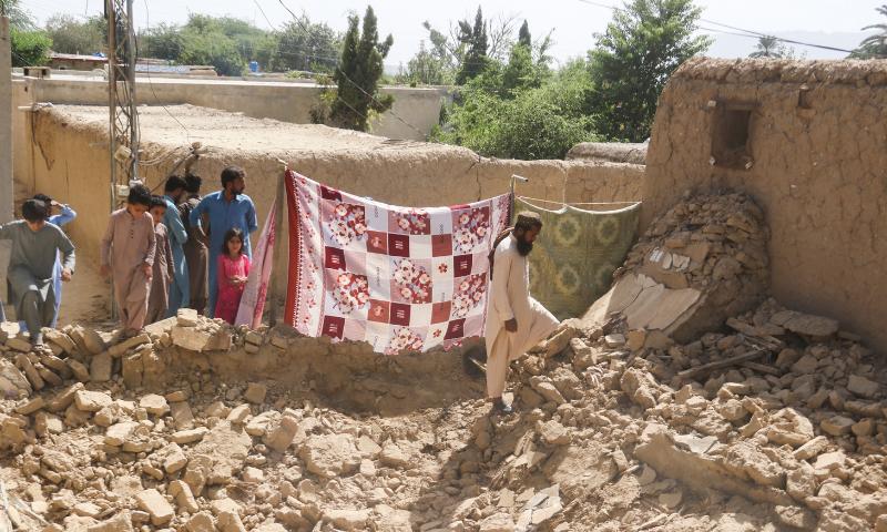 Residents gather near a damaged house following an earthquake in Harnai, Balochistan, on Thursday. — Reuters