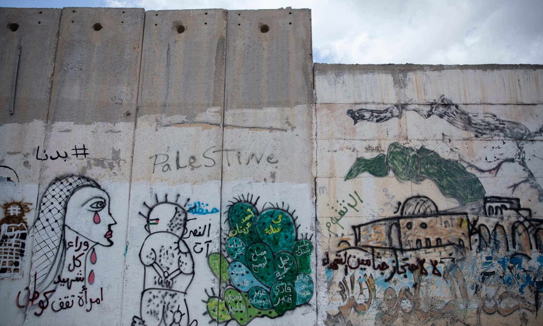 """A graffiti with names of Palestinians who were killed in conflict and Israel is holding their bodies, and reads """"no for the detention of the Martyrs remains,"""" at a section of the Israeli separation wall, in the village of Abu Dis, South of Ramallah, Palestine on September 24, 2021. — AP"""