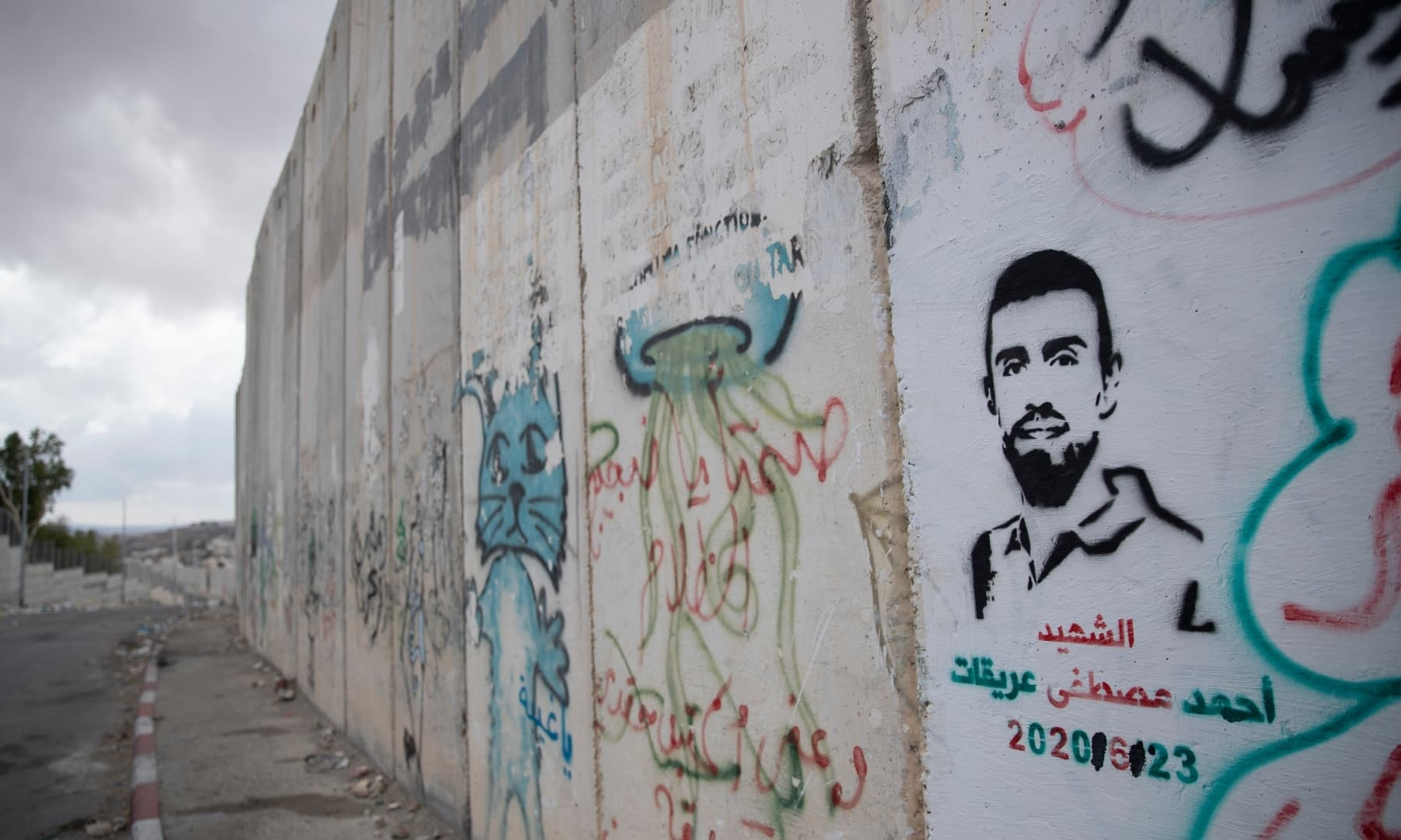 """A graffiti that depicts Ahmed Erekat, who was shot dead by Israeli forces at a West Bank checkpoint last year and held his body after, and reads """"Martyr Ahmed Erekat,"""" at a section of the Israeli separation wall, in the village of Abu Dis, South of Ramallah, Palestine on September 24, 2021. — AP"""