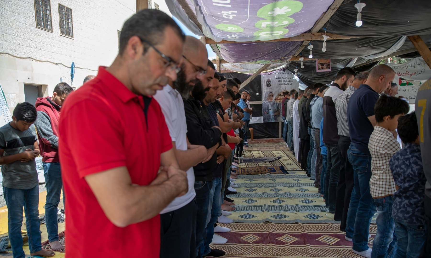 Palestinians attend Friday prayers under posters with the picture and name of Mai Afaneh, who was shot dead by Israeli forces in the West Bank last June and held her body after, in the village of Abu Dis, South of Ramallah, Palestine on September 24, 2021. — AP