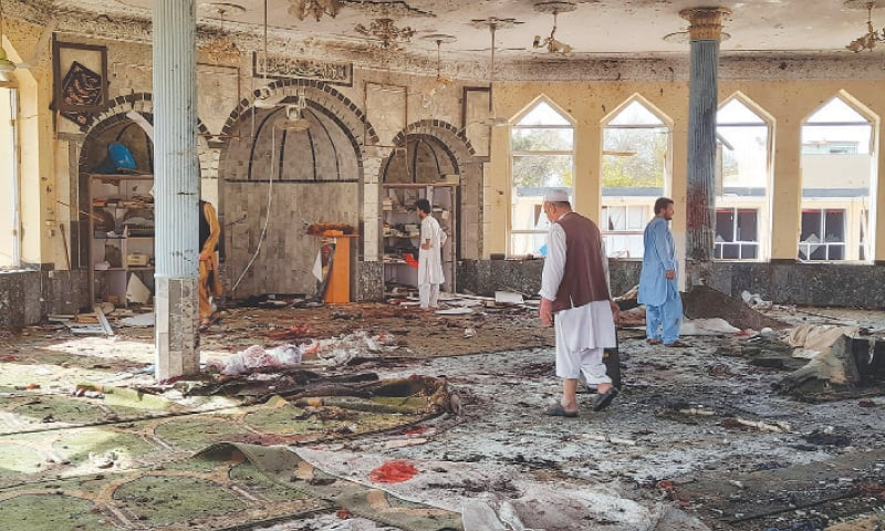 KUNDUZ: People inspect the damage inside the mosque following the bombing on Friday.—AP