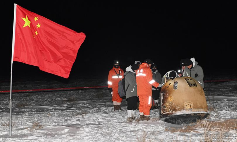 Researchers work around Chang'e-5 lunar return capsule carrying moon samples next to a Chinese national flag, after it landed in northern China's Inner Mongolia Autonomous Region on December 17, 2020. — Reuters/File