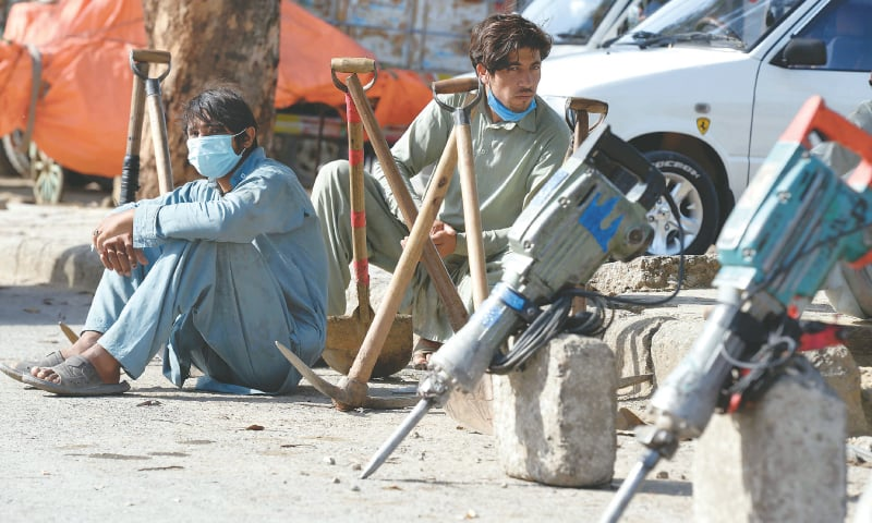 Daily wage labourers sit on a road, hoping to be picked up for a job   Mohammad Asim/White Star